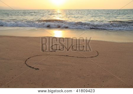 The word Love, handwritten in a sandy beach at sunset.
