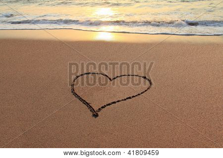 Heart in the sand on the beach at sunset.