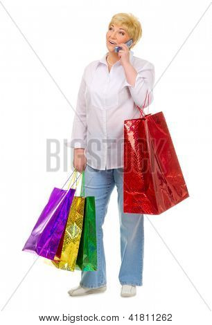 Senior woman with bags talking by mobile phone isolated
