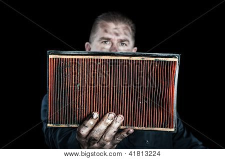 An auto mechanic holds up a filthy, grungy air filter removed from a car during normal maintenance.