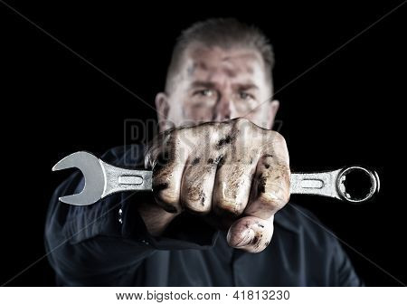 A mechanic covered in grime and grease holds out a box wrench during repairs.