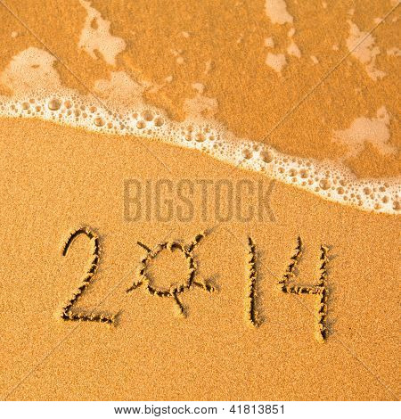 2014 written in sand on beach texture - soft wave of the sea.