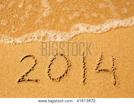 2014 written in sand on beach texture. Soft wave of the sea.