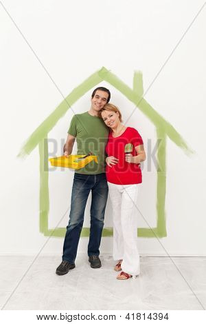 Couple expecting a baby redecorating their home - standing with painting utensils