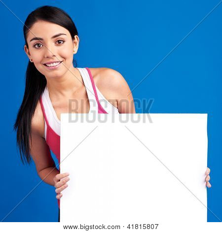 Young healthy woman holding white empty banner for copy space