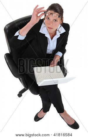 Powerful businesswoman sitting with a laptop