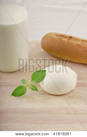 mozzarella on chopping board with tomato milk and basil