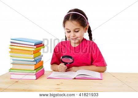 Smiling girl with books and magnifier