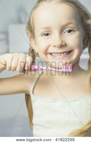 Portrait Of Little Smiling Girl Brushing Her Teeth