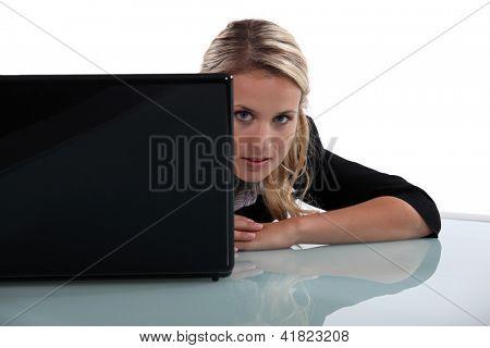 Blond woman peering from behind laptop