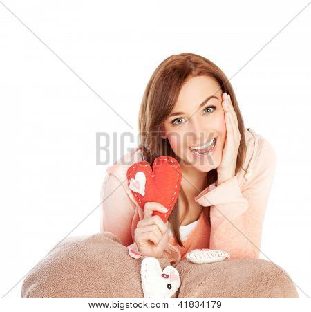 Image of lovely joyful woman sitting down and covered blanket with red handmade heart-shaped soft toy, isolated on white background, playful facial expression, Valentines day, love concept