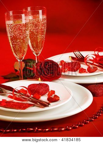 Picture of luxury table setting, romantic dinner, white festive utensil served with silverware and glasses for champagne, decorated with red rose flower and candles, Valentine day, love concept