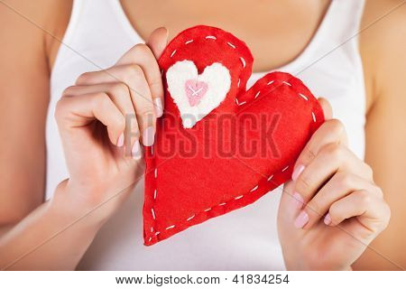 Picture of big red heart in hands, female holds handmade sewn soft toy, macro, shallow dof, woman with Valentine gift, conceptual image of health care or love