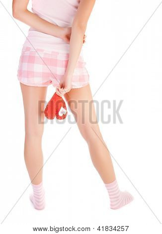 Picture of young woman holds red heart soft toy, body rear view isolated on white background, female legs, lonely heartbroken girl wearing pajamas, one-sided love and parting in relationship concept