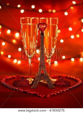 Image of two glass with romantic beverage, little eiffel tower with heart-shaped candles and beads decorated romantic table setting, honeymoon in Paris, festive lights in restaurant, Valentines day
