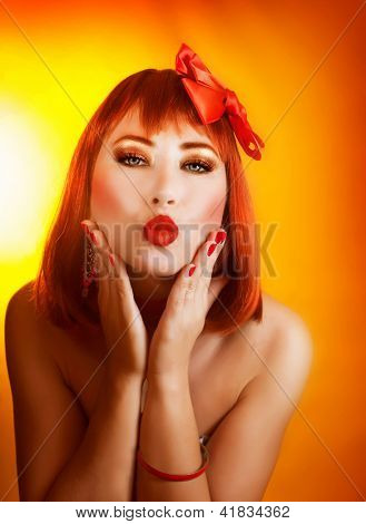 Photo of pretty redhead woman with beautiful red bow in hair isolated on yellow background, closeup portrait of attractive female with stylish makeup make kiss, Valentine day, love concept