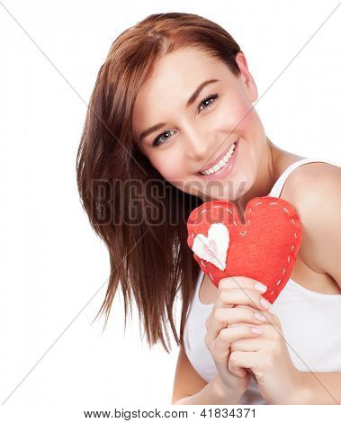Photo of cute female with brown hair holding in hand red handmade heart-shaped soft toy, closeup portrait of lovely girl with romantic present isolated on white background, Valentine day, love concept