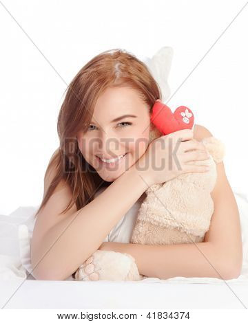 Picture of happy woman laying down in the bed, girl enjoying romantic present, soft bear and red handmade heart-shape toy as gift for Valentines day holiday, isolated on white background, love concept