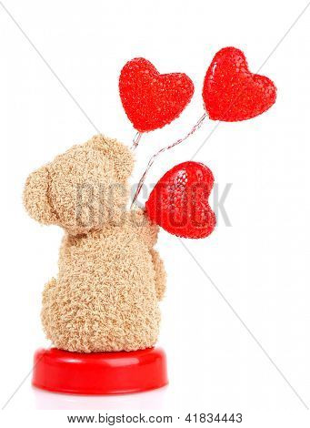 Photo of teddy bear with red heart-shaped balloon isolated on white background, back side of brown furry soft toy, romantic gift, sweet present for Valentine day holiday, love concept