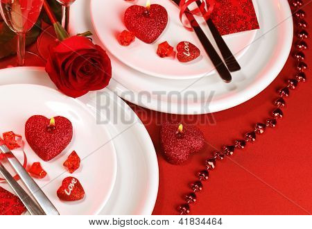 Picture of luxury festive table setting, white plate on red tablecloth served with silverware cutlery and decorated with fresh rose flower and heart-shaped candles, Valentine day, love concept