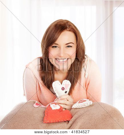 Photo of beautiful happy female sitting at home in bedroom with cute handmade hearts soft toy, symbol of love, romantic gift, Valentine day, present for holiday, affection and happiness concept