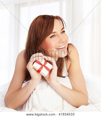 Photo of cute woman enjoying gift, closeup portrait of pretty female at home holding in hands little white present box with red ribbon, Valentine day, romantic holiday, love concept