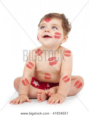 Photo of happy kid covered with red kisses print on the body, adorable baby boy sitting in studio isolated on white background, nice toddler looking up, Valentine day, love concept