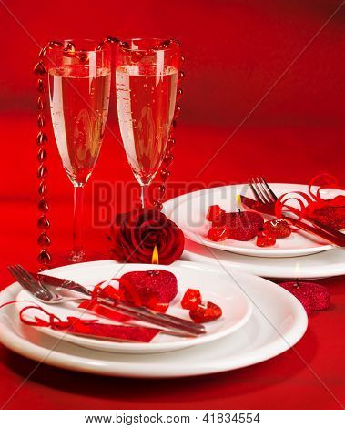 Image of romantic dinner, white festive plate served with silver cutlery and wineglasses and decorated with heart-shaped candle and red fresh roses, Valentine day, romance and love concept