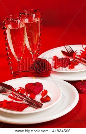 Picture of red holiday table decoration, white luxury dinnerware served with knife and fork, two glass for champagne, sparkling wine, romantic dinner, Valentines day, romance and love concept