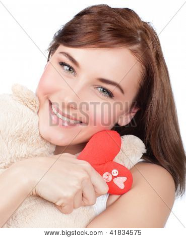 Photo of pretty woman hug cute soft toy, closeup portrait of pretty brunette female with teddy bear and red handmade heart isolated on white background, Valentine day, love and happiness concept