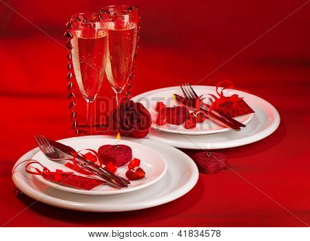 Photo of festive table setting, luxury white dishware on red tablecloth, hearts decorations, beautiful rose flower, two glasses for wine, alcohol drink, romantic date, Valentine day, love concept