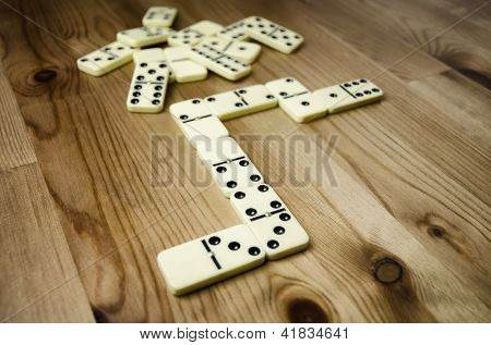 Close up of domino with black dots on wooden background