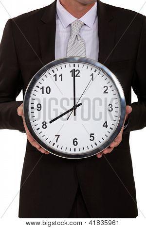 Uma imagem recortada de um empresário segurando um relógio.