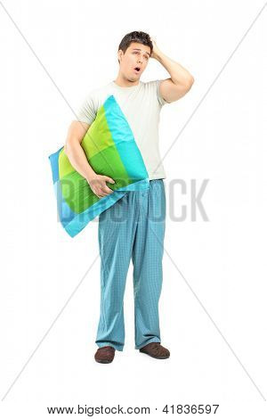 Full length portrait of a young man in pijamas feeling sleepy isolated on white background