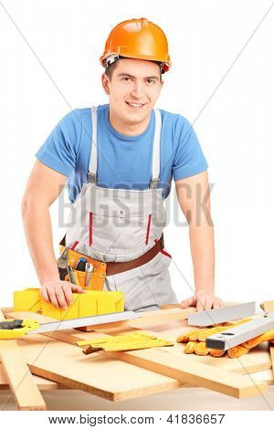 Manual woker standing next to a table with equipment and wooden pieces isolated on white background