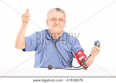 Happy senior man measuring blood pressure and giving a thumb up isolated on white background