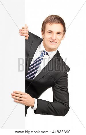 Young businessman posing behind a blank panel isolated on white background