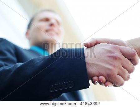 Business people shaking hands. Bright modern building background. Focus on hand.