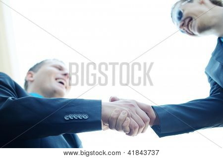 Business shaking hands in front of modern building with copy space (selective focus)