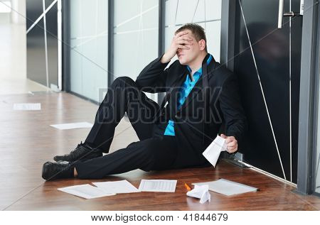 Portrait of a stressed disappointed businessman sitting alone on floor in office