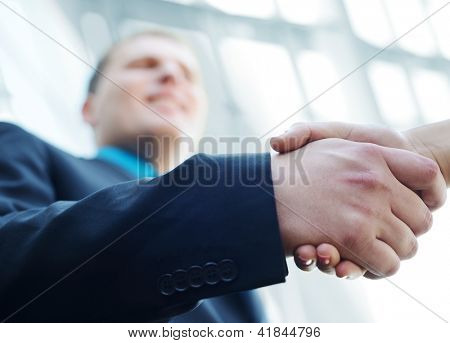 Business people shaking hands. Bright modern building background.