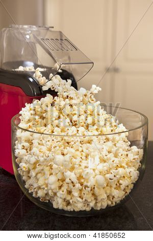 Bowl of popcorn with popcorn machine on a kitchen bench.  Healthy home-made snacking.