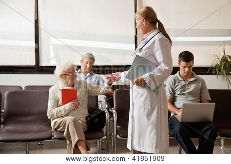 Mature female doctor holding hand of senior woman while people sitting in hospital lobby