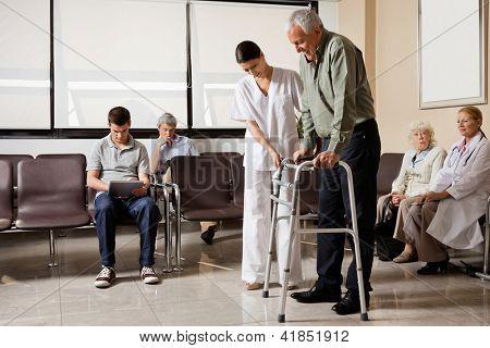 Alter Mann, die von weiblichen Krankenschwester zu Fuß von den Zimmer-Rahmen mit Leute sitzen in Krankenhaus Lob unterstützt wird