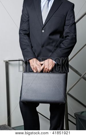 Midsection of young businessman carrying briefcase by steps