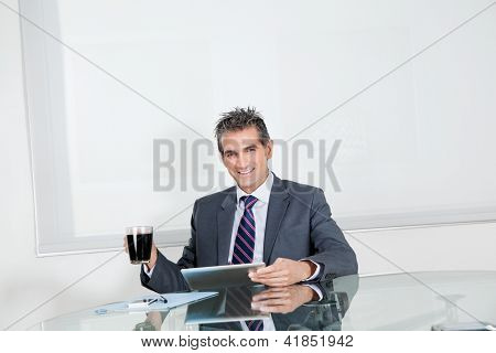 Portrait of mid adult businessman with coffee cup using digital tablet at desk in office