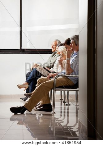 Group of people sitting in waiting area of hospital