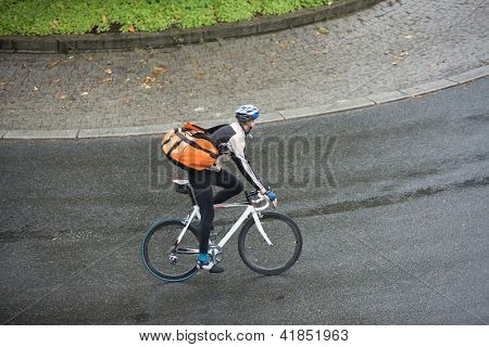 Man in protective gear with backpack riding bicycle on street