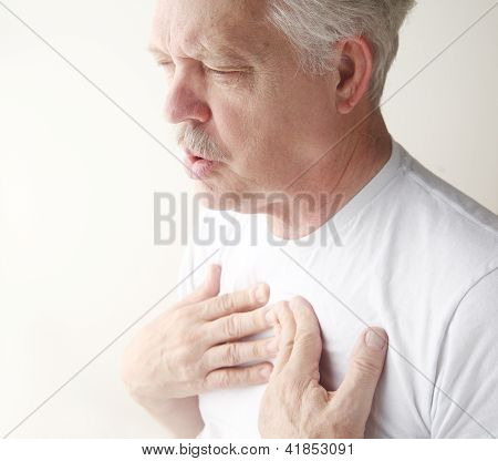 man exhales with hands on chest