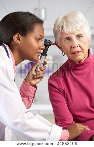 Médico orejas examinador Senior del paciente femenino